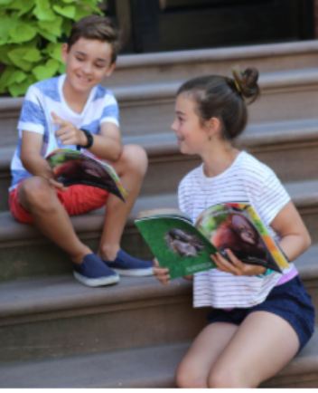 Henry Kurzawa and Maeve Igoe, PS 107 5th graders, celebrate the successful rescue of orphaned orangutan Budi while reading their newly published book. Photo courtesy of Ericka Novotny.